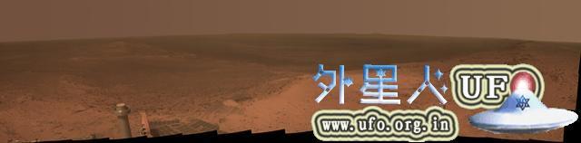 """图中显示的景象来自机遇号的摄像机,背景为火星""""奋进""""撞击坑的边缘顶部"""