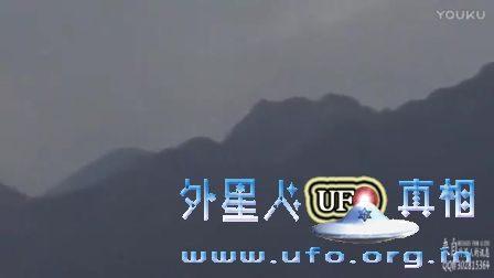 小山丘上UFO飞碟缓慢飞行 尾部有灯光似萤火虫的图片